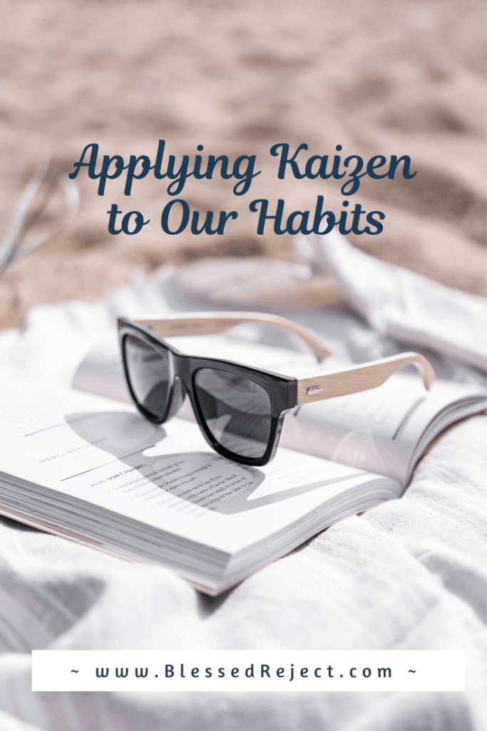Apply Kaizen to our habits, pictured with sunglasses resting on an open book.